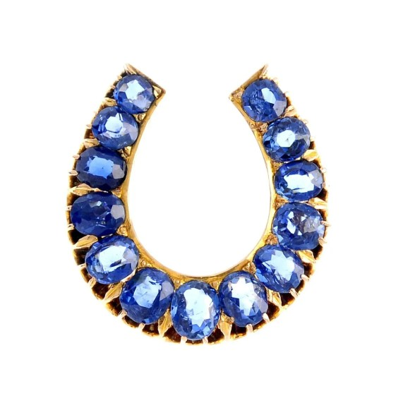 An early 20th century gold sapphire horseshoe brooch.
