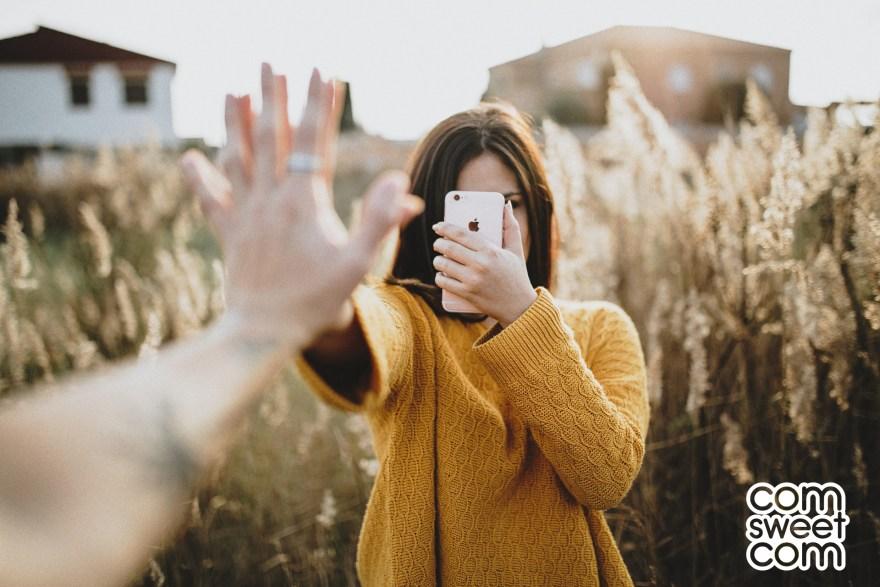 Jeune femme au pull jaune avec un iPhone dans un champ de blé. Com Sweet Com - Agence à taille humaine de conseil en Design Graphique, webmarketing et community management. Vous conseiller dans votre communication ! 🚀