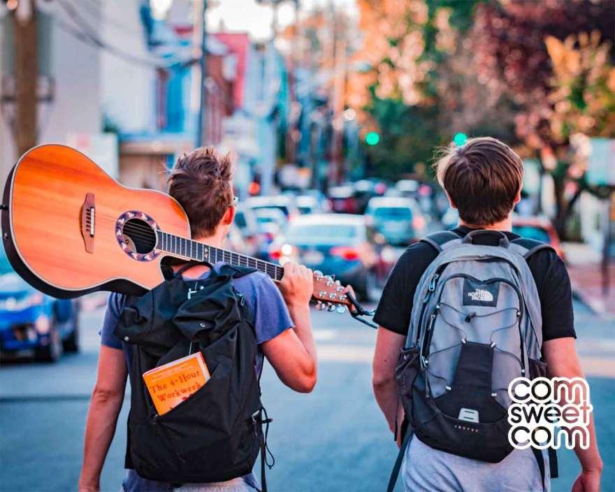 Deux jeunes hommes en voyage avec leur sac à dos et une guitare -  - Marketing d'influence Agance Com Sweet Com - Design Graphique, webmarketing, Social Media Management