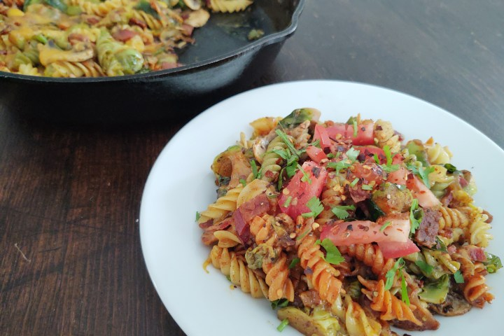Cheesy Brussels Sprouts Carbonara with Bacon and Mushrooms dressed with tomato and cilantro