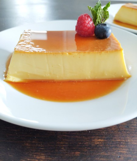 Flan displayed on a white plate with fresh fruit on top