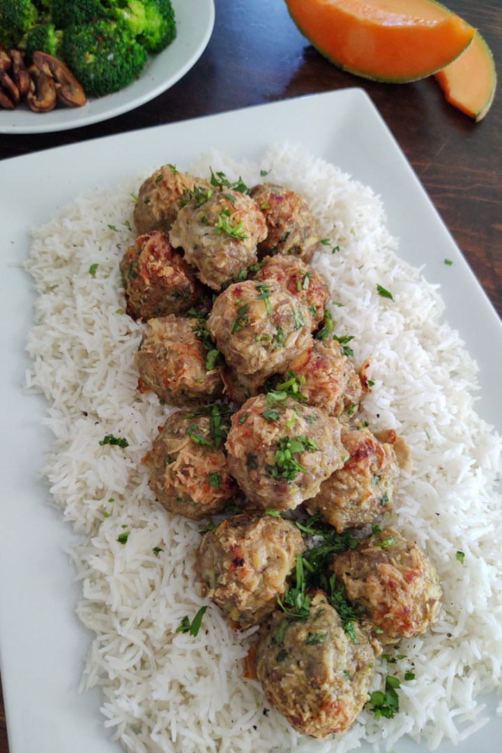 Meatballs presented on a bed of rice with broccoli and cantaloupe displayed above