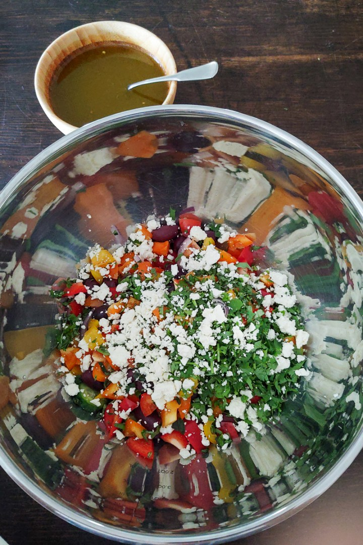 ingredients of mediterranean salad in bowl before mixing in dressing