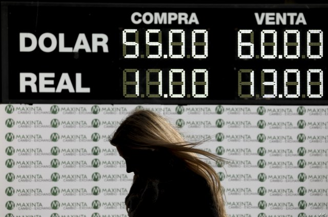 A woman walks past a currency exchange board in Buenos Aires, Argentina, Aug. 12, 2019.