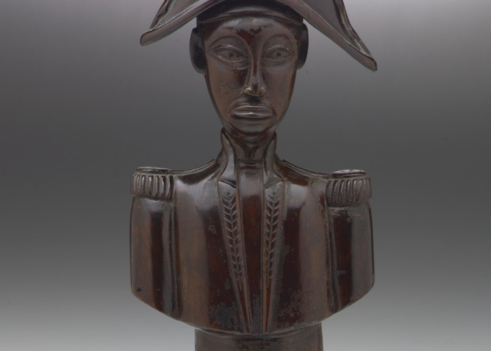 A wooden, sculpted bust of Jean-Jaques Dessaline, he is dressed in military uniform with a feathered, bicorne hat. His face is quite narrow and stylised.