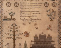 A square piece of fabric which has been embroidered with images of a tree, a building and a poem with a floral border.