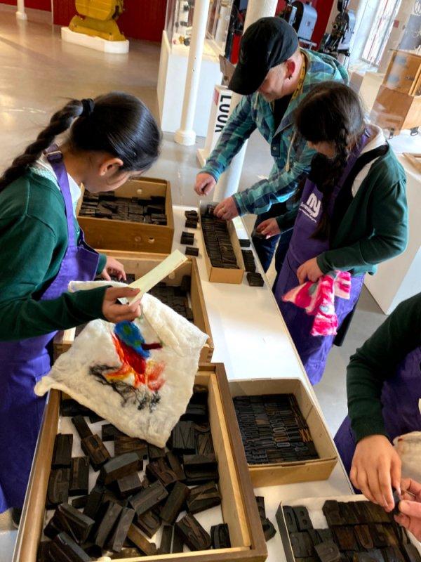 students choosing printing blocks to create their slogans