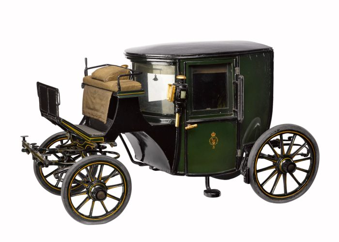 A photograph of a green carriage against a white background