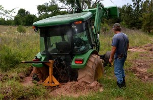 On May 12, Ken Holland, East Texas farm hand, surveys a tractor he and his boss, Malcom Williams, have been trying to get unstuck for weeks. A week ago, Williams said he had two other tractors stuck trying to pull this one out. (Texas A&M AgriLife Extension Service photo by Robert Burns)