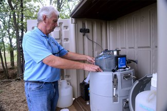 Andrew Sharpley, professor of crop, soil and environmental sciences, calibrates an automated water sampler for a sampling site along a stream in a farm field.