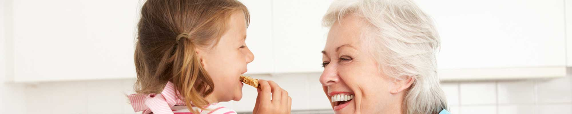 Happy, Smiling Aging Woman Baking Cookies with a Little Girl