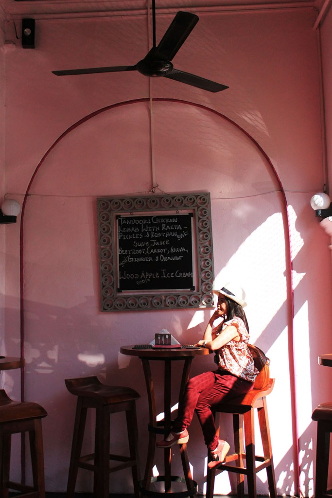 fashionable female traveler in the empire cafe sri lanka dressed in red and pink