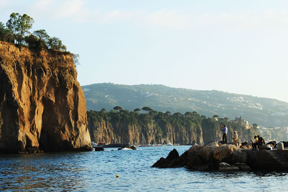 People fishing in a private beach in Sorrento, Italy during summer