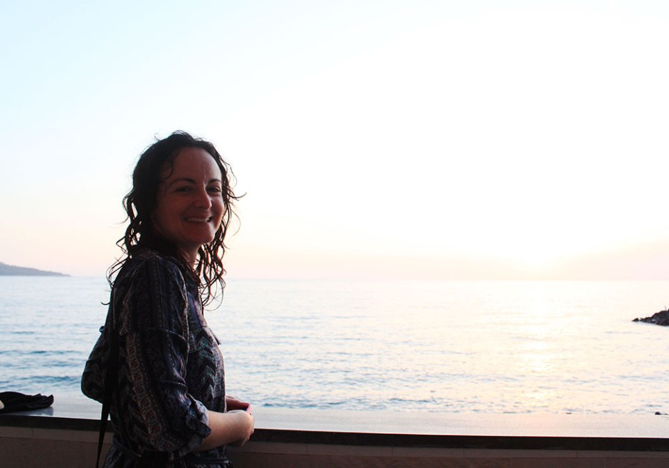 A woman smilling from her balcony during summer holiday in Sorrento, Italy with sea background.