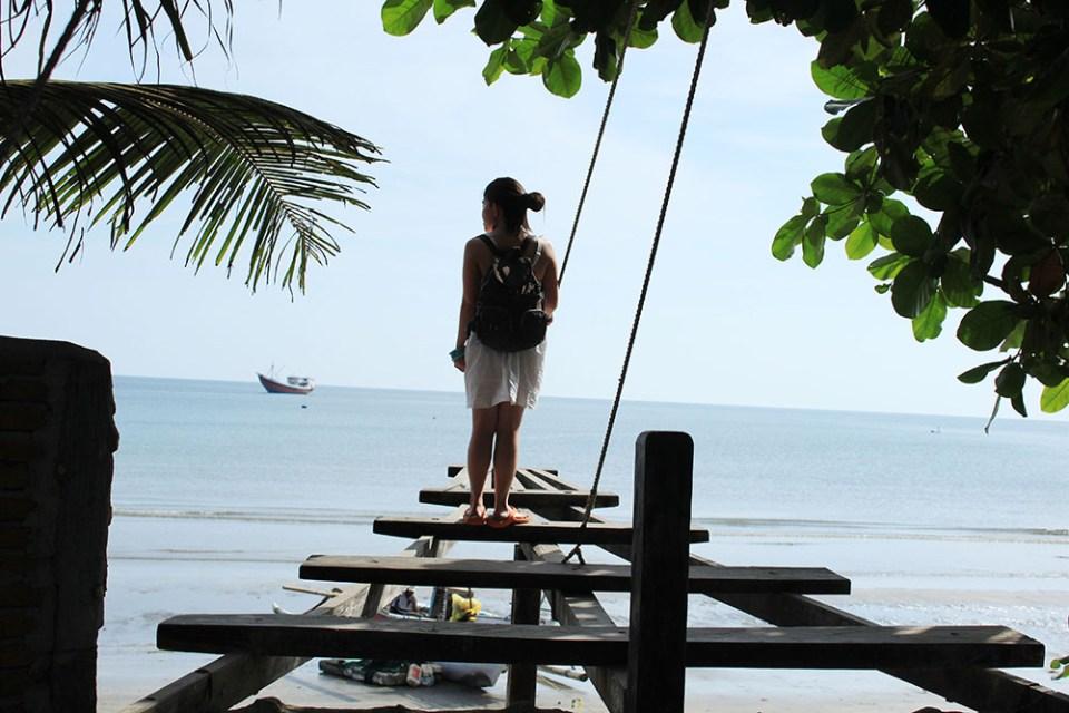 An adventurous girl with The Latte Factor Dream Bucket List standing at the edge of a beach bridge