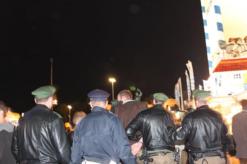 thief bad guy caught by policemen oktoberfest luna park at night munich germany