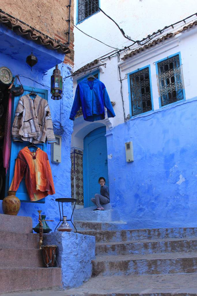 girl pointing finger chefchaouen blue walls building clothes morocco_agirlnamedclara