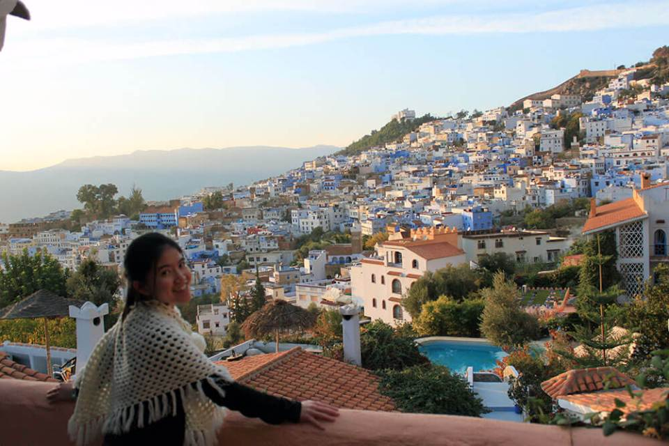 asian girl smiling rooftop chefchaouen the blue city morocco sunset buildings_agirlnamedclara