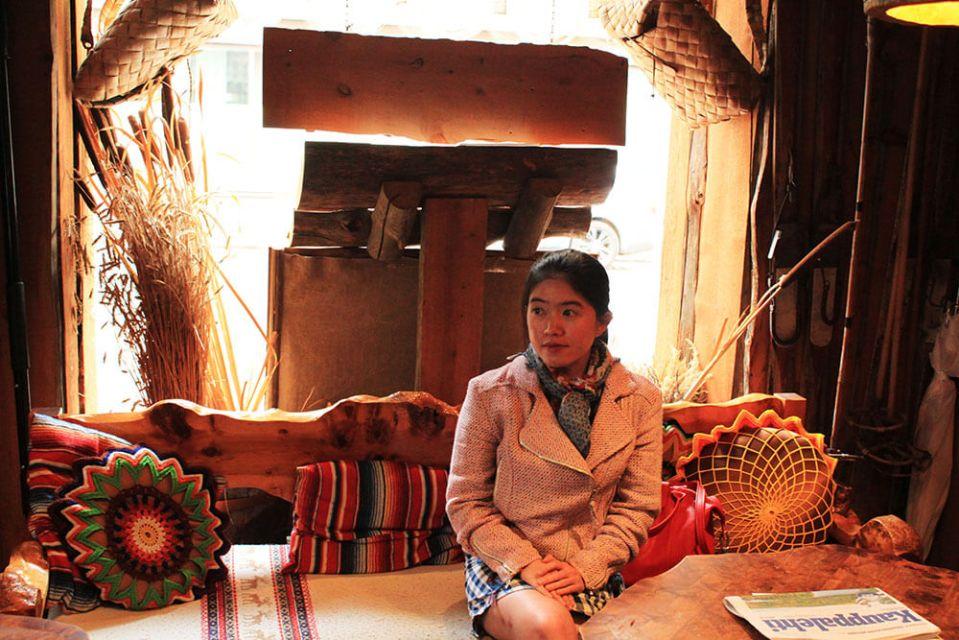 girl solo travel pink wool jacket sitting scandinavian interior rustic finland agirlnamedclara
