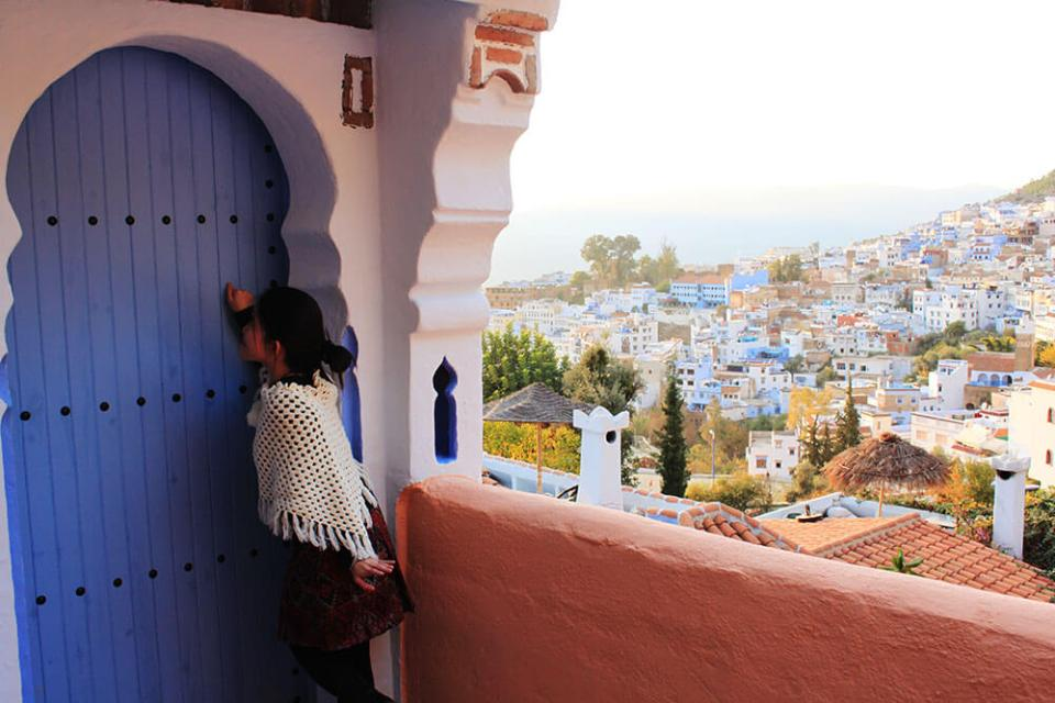 agirlnamedclara_asian girl traveler knocking blue door chefchaouen blue city morocco morning