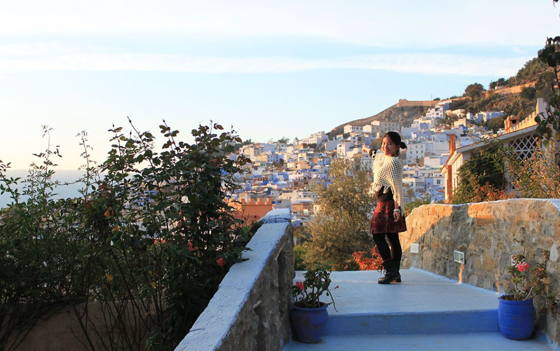 agirlnamedclara_asian girl traveler standing on blue bridge chefchaouen morocco sunset buildings backgrounds