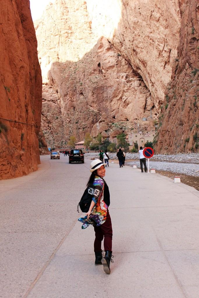 todra gorge morocco asian girl white fedora colourful scarf backpack walking smiling agirlnamedclara