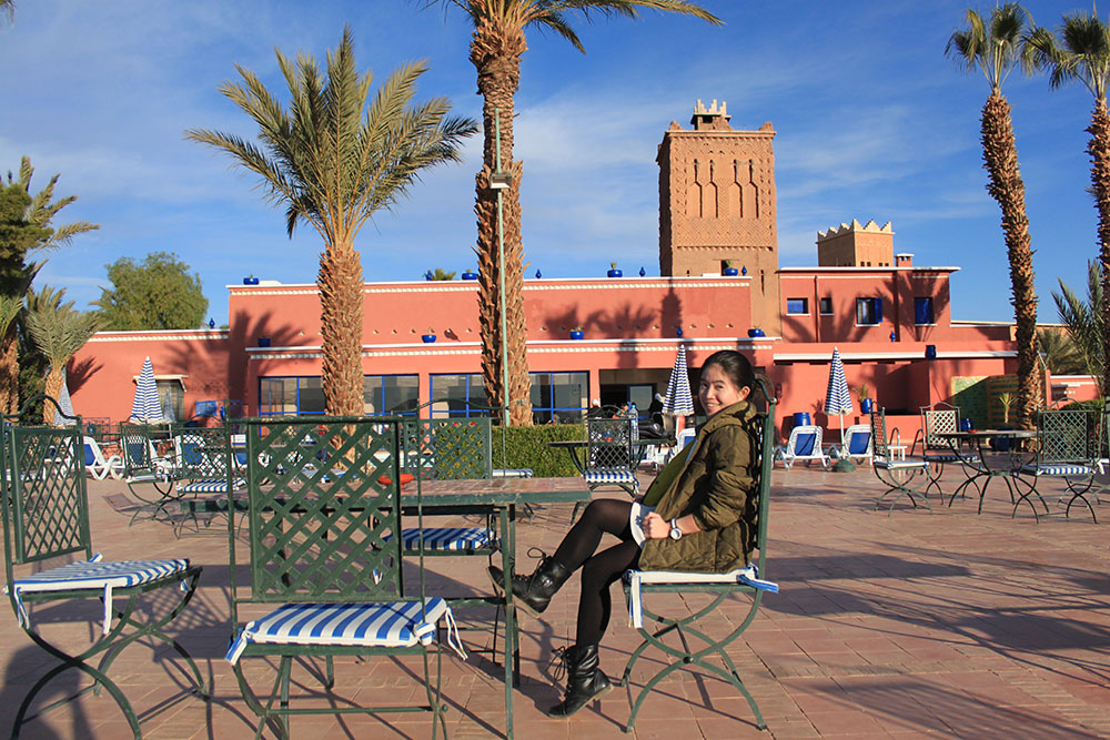 agirlnamedclara asian solo female traveler pose morocco hotel background marrakech palm tree swimming pool