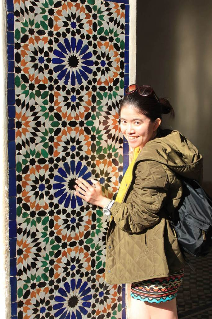 Bahia Palace Palais Bahia Morocco female asian traveler standing smiling with colorful tiles wall agirlnamedclara