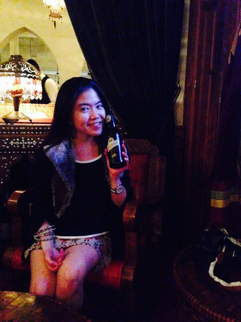 asian girl solo traveler long hair smilling sitting on the chair holding a beer bottle rick's cafe casablanca morocco agirlnamedclara