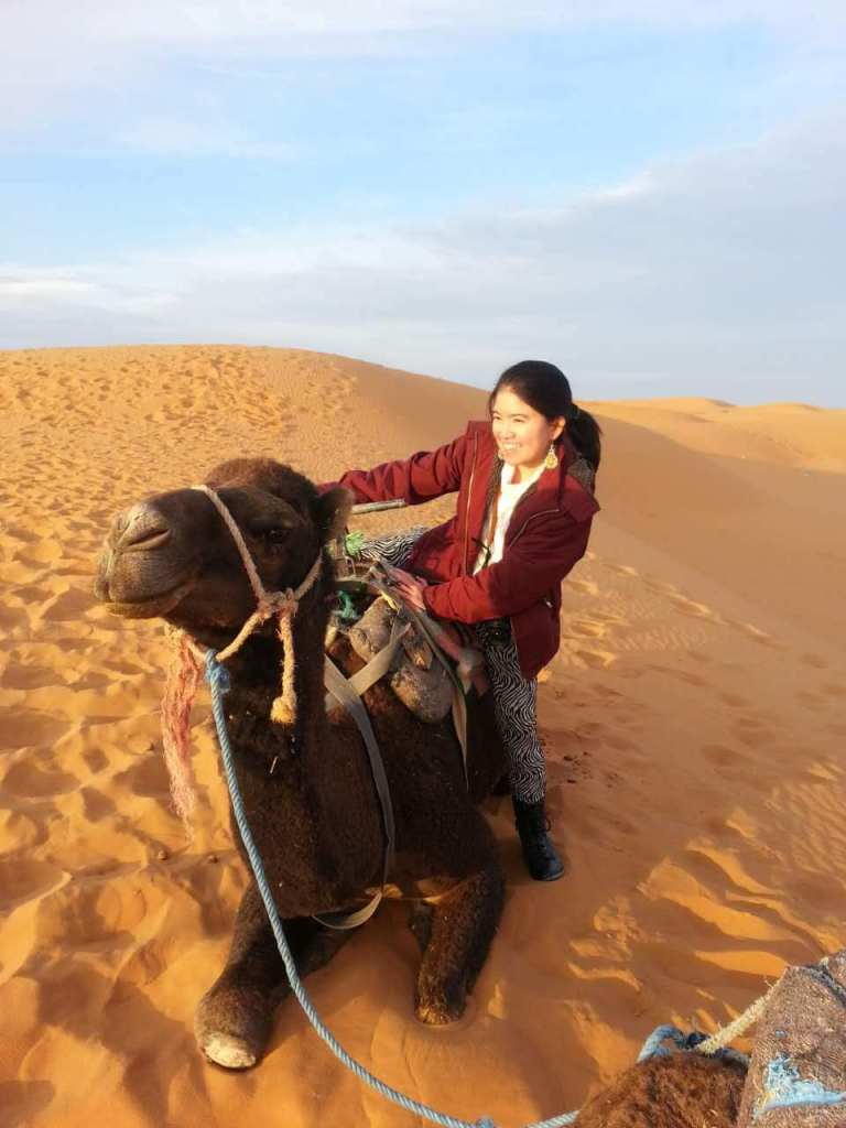 little girl asian red jacket smiling happy riding camel sahara desert morocco agirlnamedclara