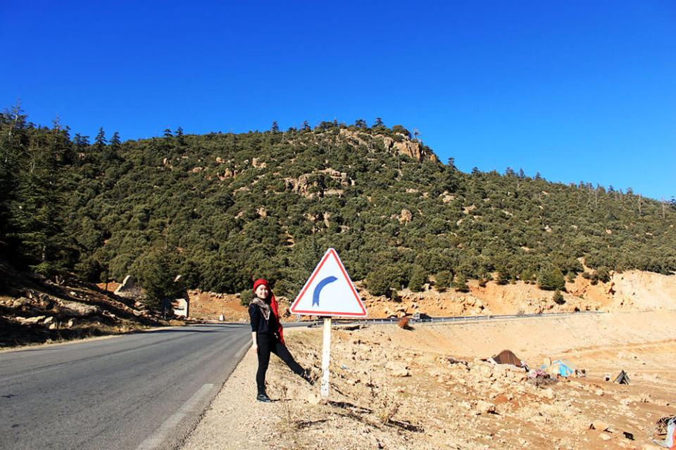 girl in black red head scarf standing roadside road sign mountain background blue sky morocco