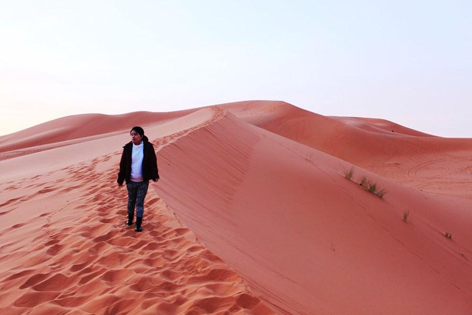 little asian girl walking alone in sahara desert sunrise morocco