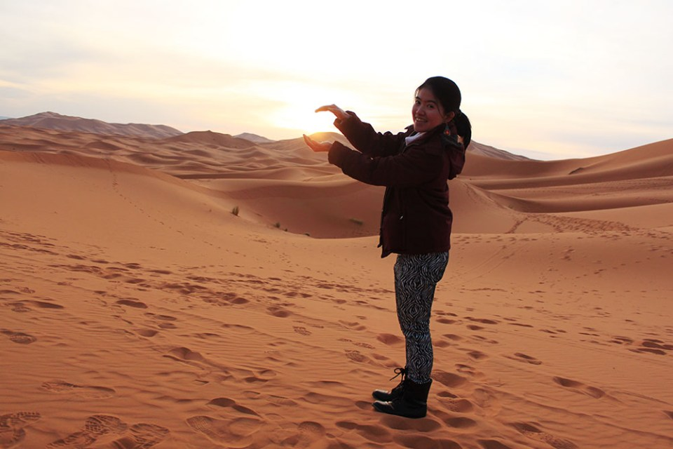 catching sunrise between palms asian girl solo traveler sahara desert morocco sunrise