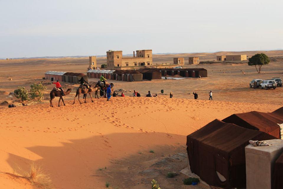 tourist on camel ride small local village sahara desert morocco agirlnamedclara