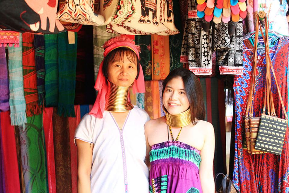 asian girl tourist traveler pose with local long neck woman chiang mai with colorful textile background thailand agirlnamedclara
