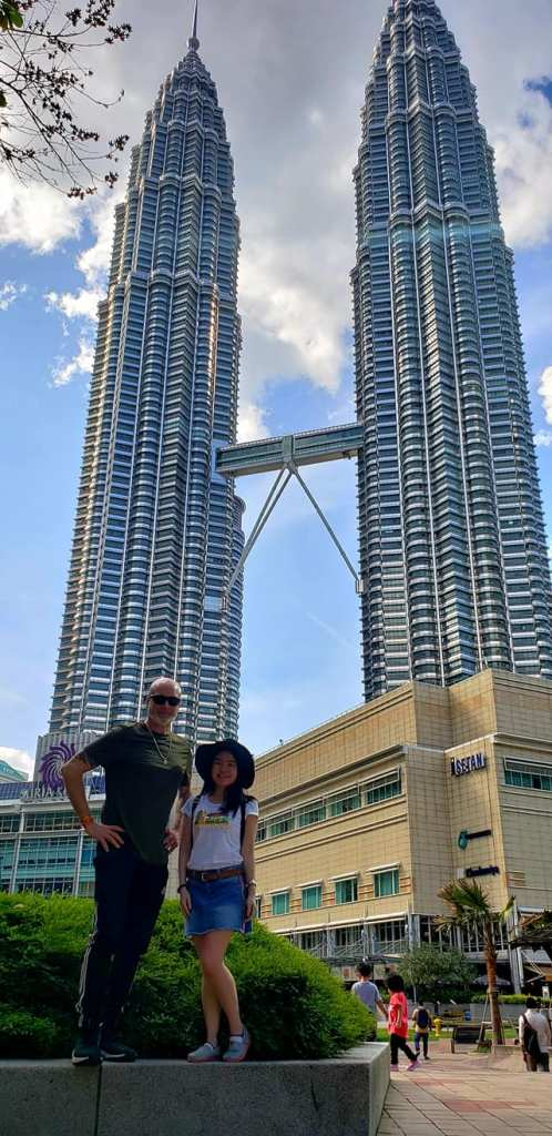 couple traveler pose petronas twin towers background blue sky kl express travel itinerary agirlnamedclara