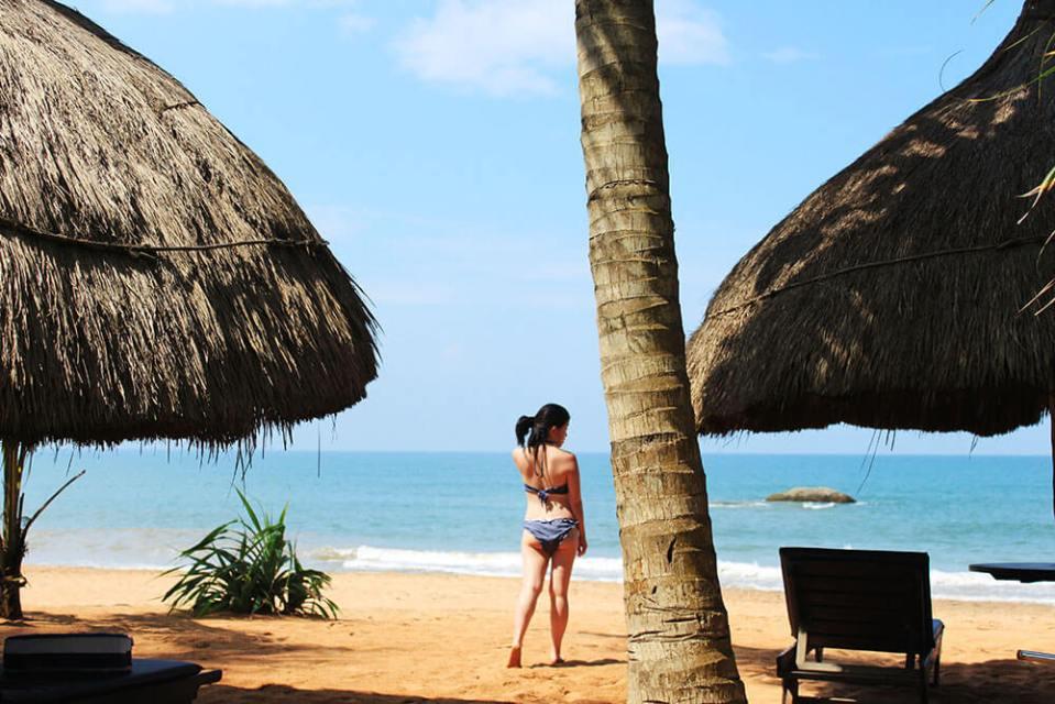asian girl hairbun facing back blue bikini white sand beach straw huts bentota sri lanka agirlnamedclara