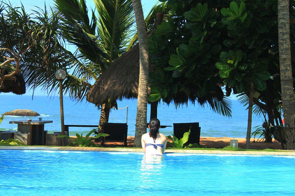 girl in blue bikini facing back blue sky coconut tree hut background morning agirlnamedclara sea rock villa bentota sri lanka