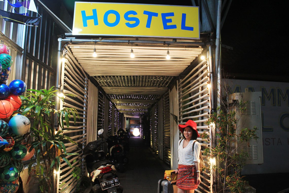 a guide to choosing a hostel seminyak bali asian girl traveler red hat skirt white shirt holds luggage standing at hostel entrance agirlnamedclara