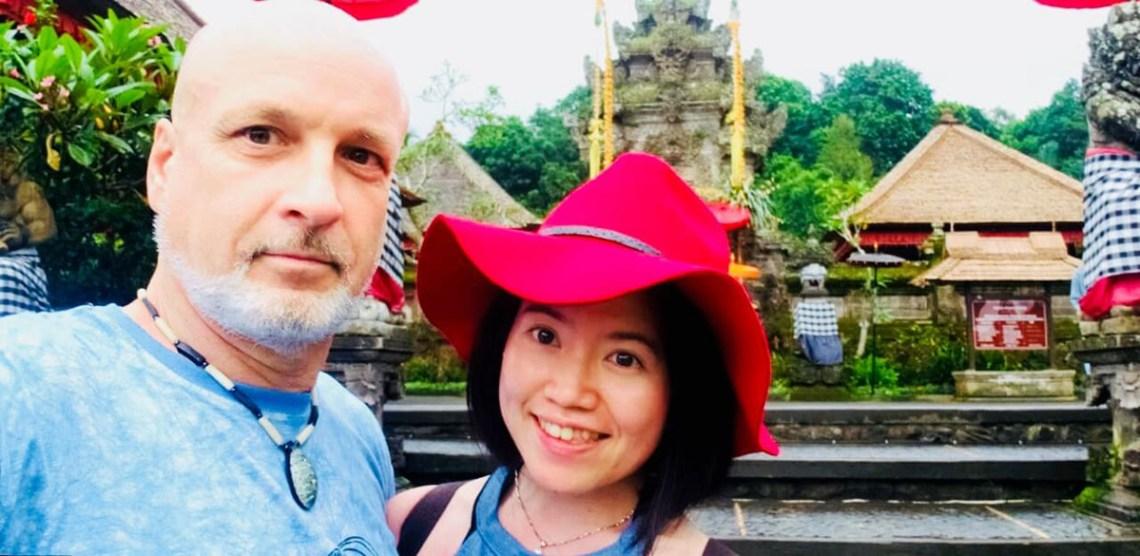 age gap couple smiling desa penglipuran village entrance bali galungan festival agirlnamedclara