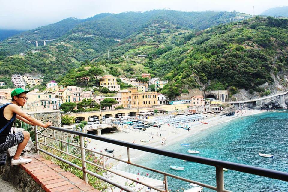 asian man standing on top looking at monterosso cinque terre beach colorful houses italy agirlnamedclara
