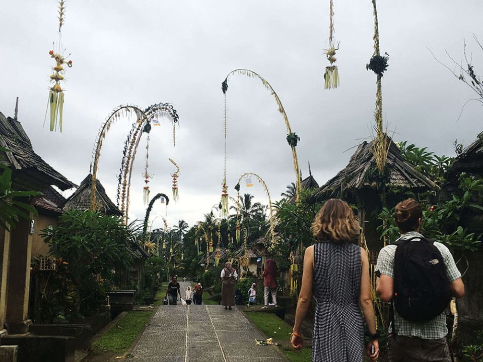 causian tourist couple walking at desa penglipuran village bali galungan festival agirlnamedclara