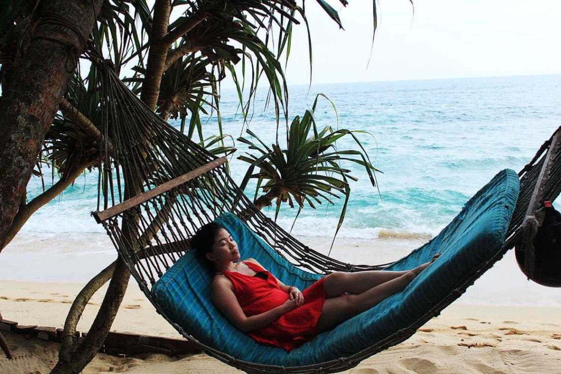 asian girl red dress sleeping on hammock beach blue sea background sri lanka_agirlnamedclara