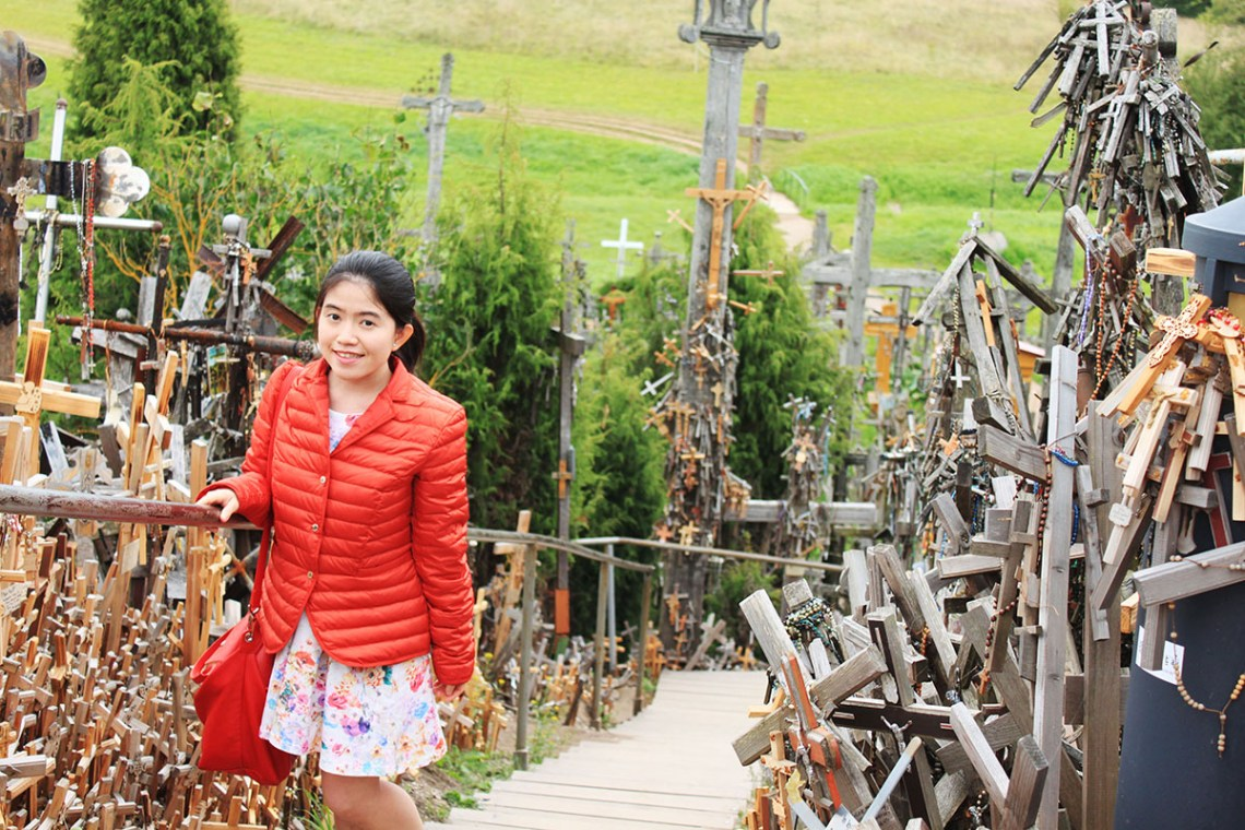 asian little girl smilling orange downjacket flower dress standing surrounded by crosses Hill of Crosses Lithuania Happy Easter_agirlnamedclara