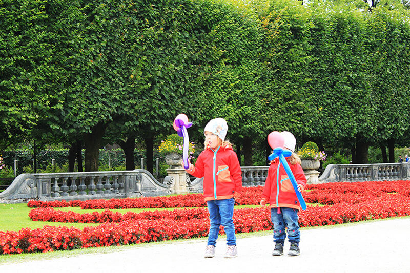little girls playing balloon red sweater red flowers mirabell gardens austria_agirlnamedclara