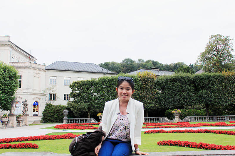 small asian girl solo travel smiling white blazer sitting mirabell gardens background_agirlnamedclara