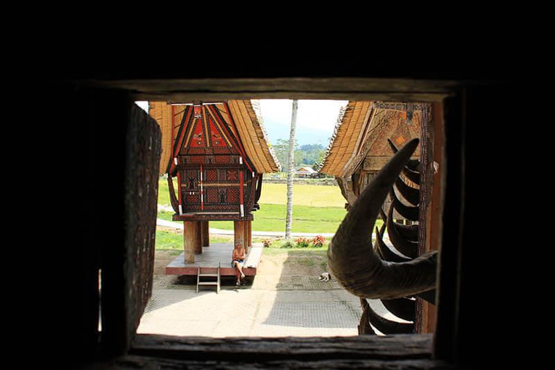 a view from tongkonan window local man sitting kete kesu toraja indonesia_agirlnamedclara