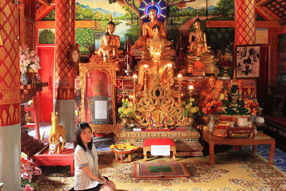 asian girl short black hair sit on the floor in buddhist temple giant gold buddha statue chiang mai thailand_agirlnamedclara