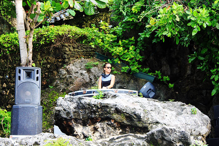 female dj with sunglasses on natural cliff rock bar bali_agirlnamedclara