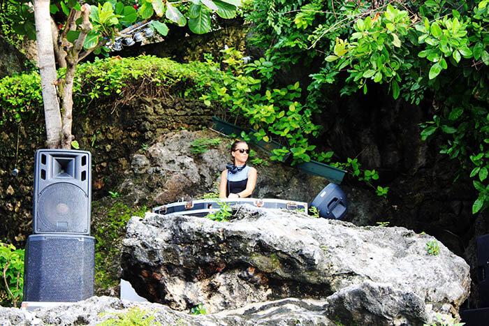female dj with sunglasses on natural cliff rock bar bali_agirlnamedclara
